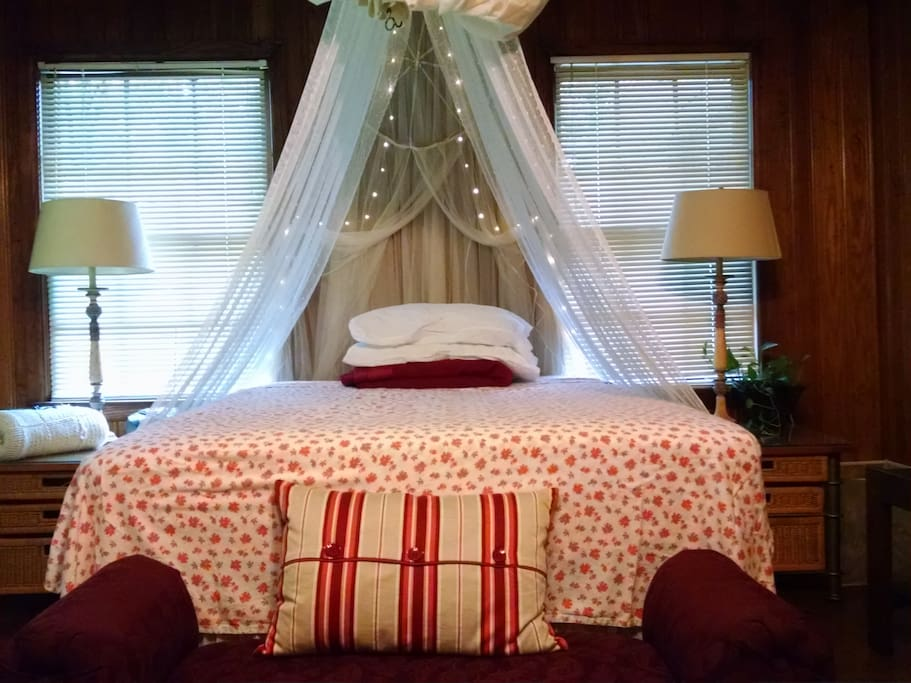 Queen bed with privacy curtains and lights.