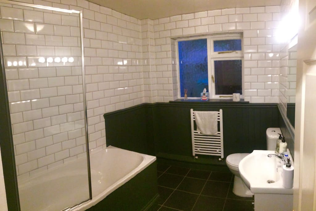 Modern bathroom, bath and electric shower.