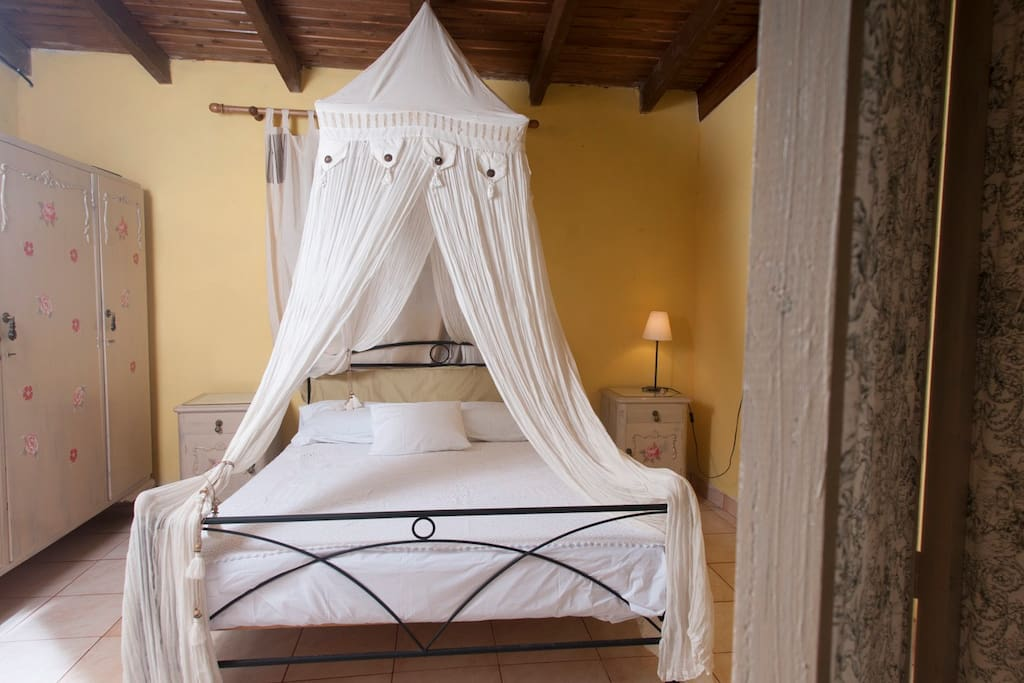 the main bedroom has a very warm decoration with a king size bed  and a sofa that can become a double bed