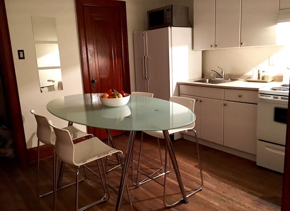 Kitchen with microwave, toaster, coffee maker, kettle, and cooking and serving dishes.
