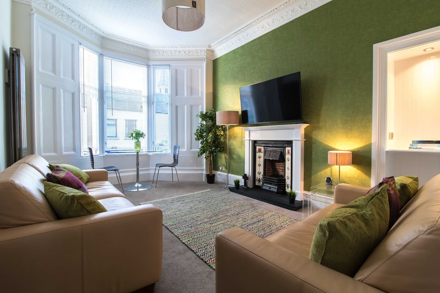 Boutique Victorian Living room with bay window dining. Featuring original decorative fireplace, computer desk centre, Virgin Fibre Broadband and Ethernet port, along with leather two and three seater sofas beside  traditional  column radiators.