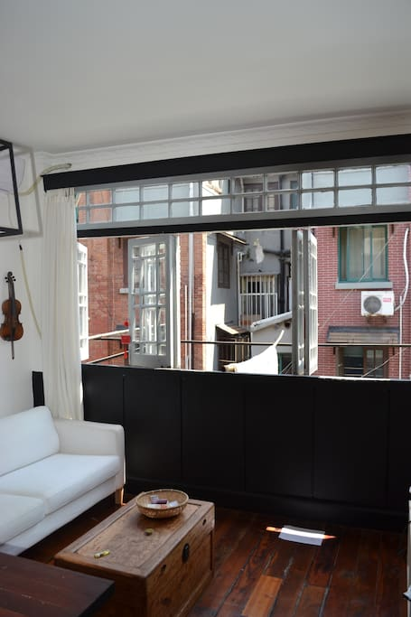 Living room with a large bay window on the 1st floor over looking an old traditional Shanghaiese street (no buildings, only two-three storeys Shanghaiese lane houses)