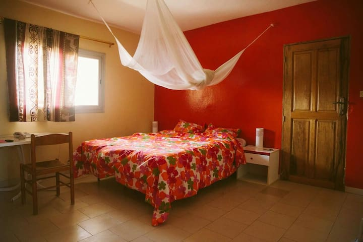 the master room, with a large bed, desk and mosquito net.