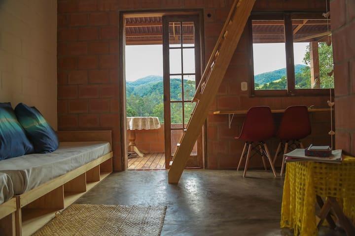 Sala, varanda ao fundo, escada para mezanino, mesa da cozinha.