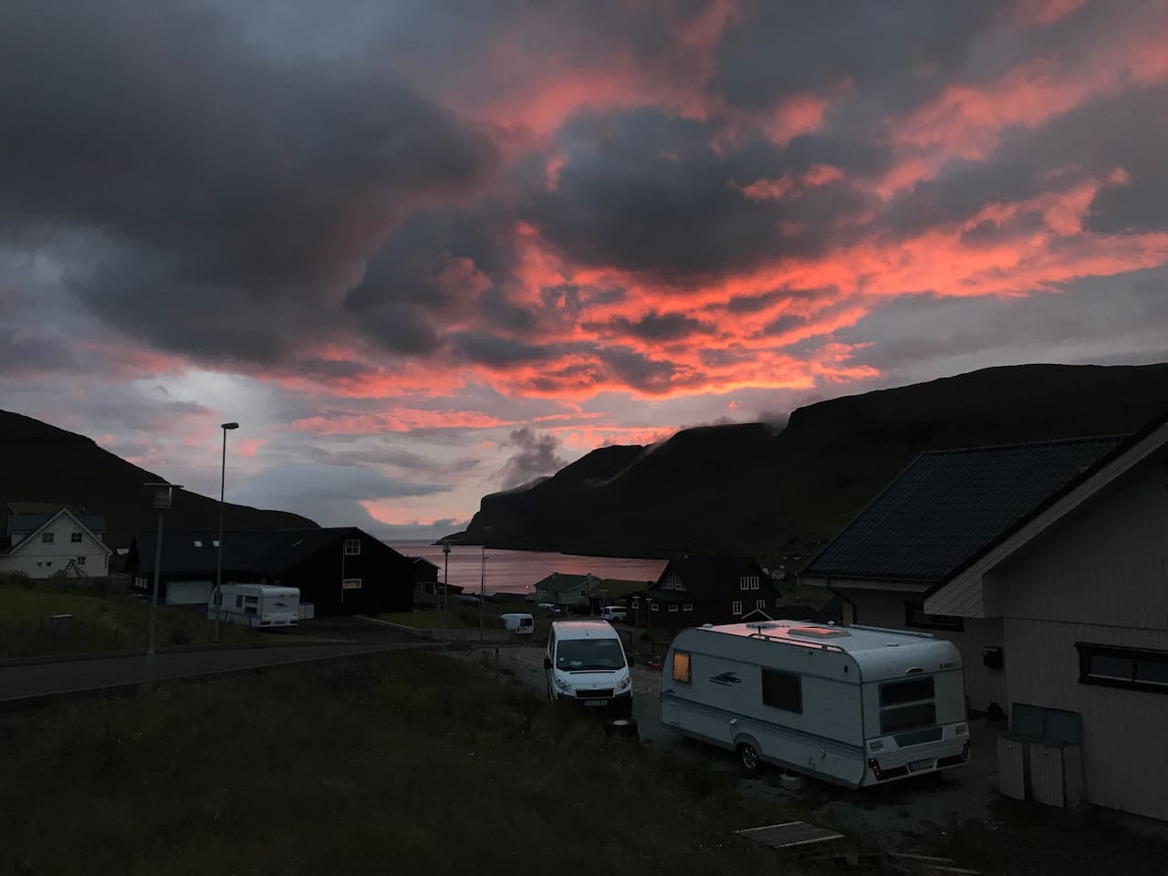 Our house and the camper. Mykines in the background, under the red skies.