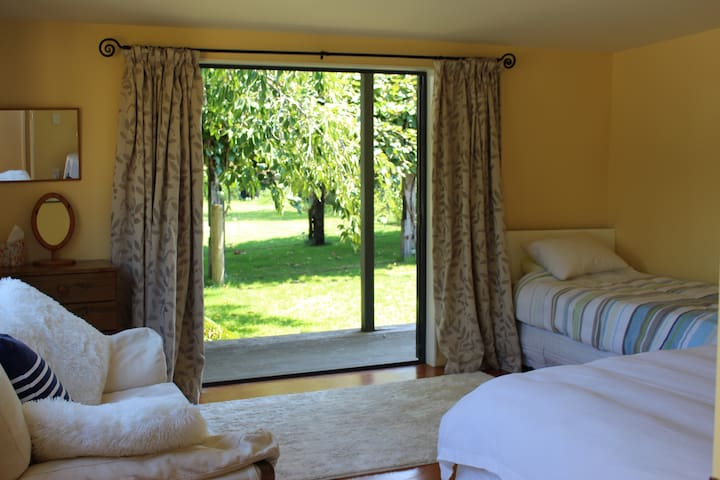 Large bedroom with Queen bed and single bed and a comfy sofa overlooking the garden and kiwi fruit canopy