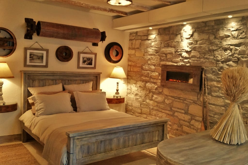 Fall asleep listening to the river on the comfy farmhouse style bed with memory foam mattress and top quality bedding. Original limestone wall and electric fireplace along with mill artifacts adorn the space.