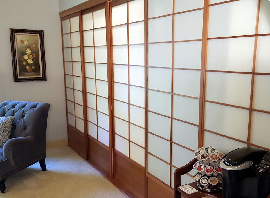 Beautiful Japanese shoji doors open to a spacious closet and are backlit to provide ambient lighting