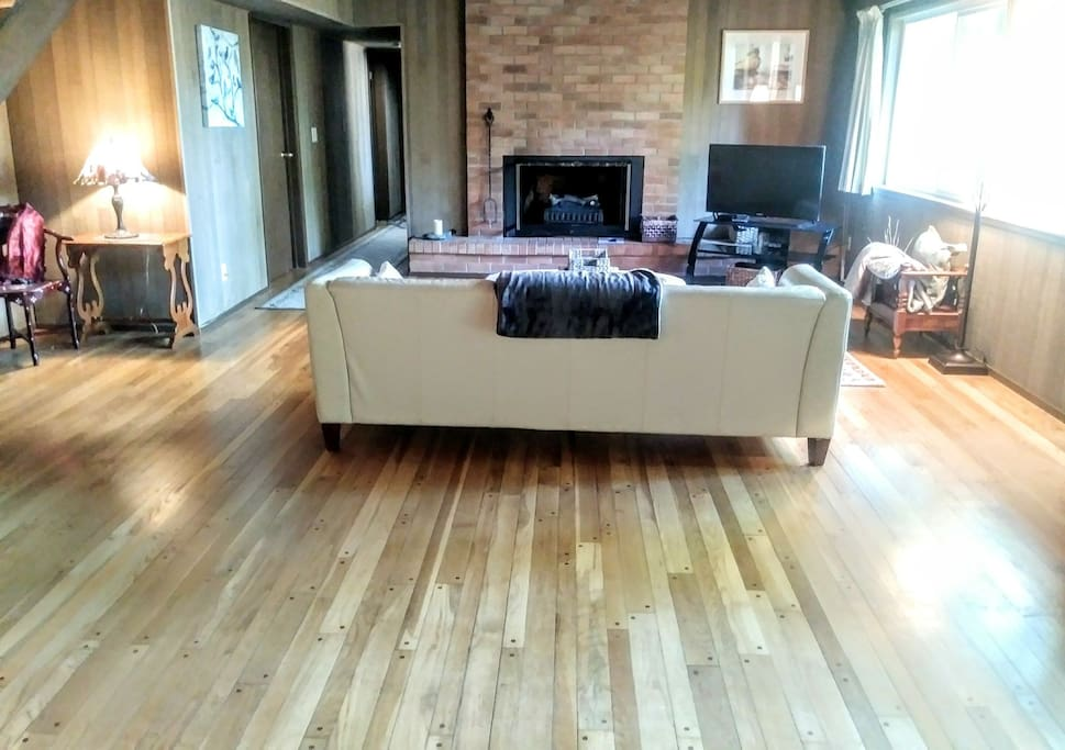 Living Room with brick fireplace, TV, WiFi and breathtaking view of a private back yard.