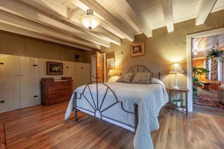 Queen sized bed with luxury mattress and bedding in a sunny, private room.
