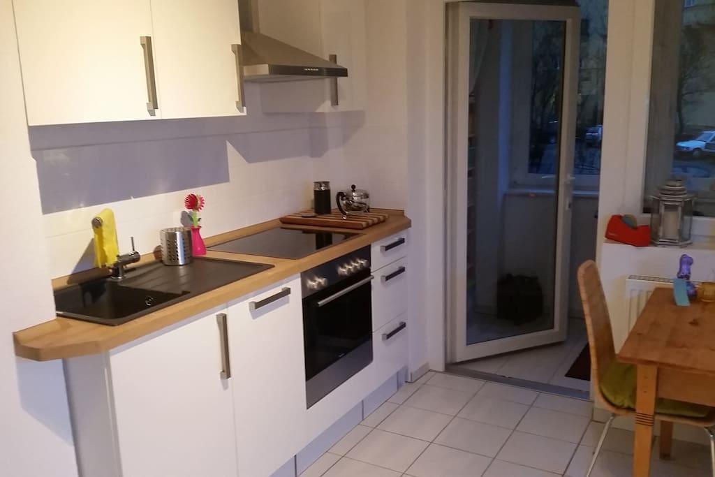 Küche mit Cerankochfeld, Herd und Blick zur Logia / Kitchen with hob, oven and views to Logia