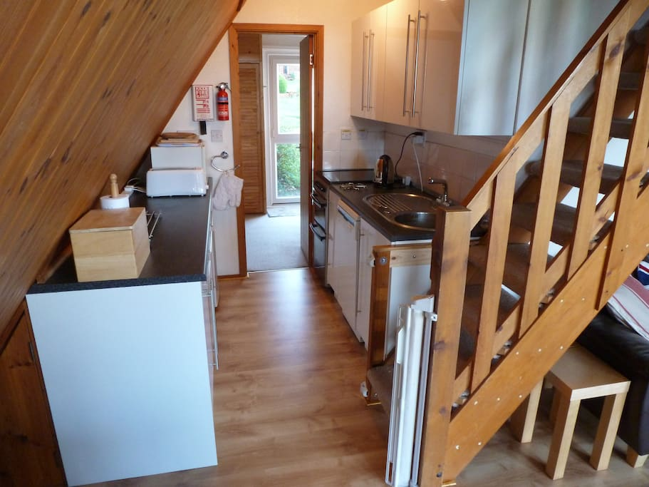 Fully equipped kitchen leading to separate dining room with freezer and washing machine.