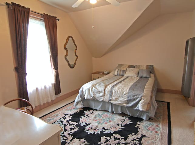 Master bedroom featuring queen-sized bed and view over the town