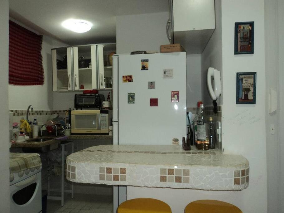 Cozinha equipada com fogão, geladeira, forno elétrico e microondas e máquina de lavar
