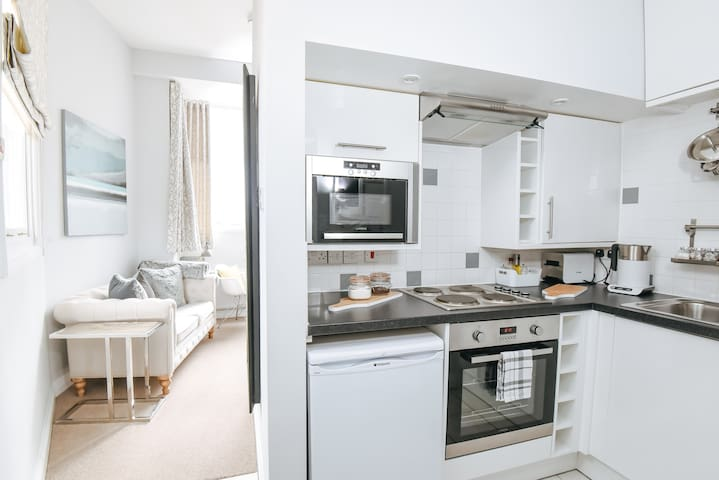 Kitchen with fridge (& freezer section), conventional oven, hob, microwave oven, toaster / kettle and crockery & cutlery.