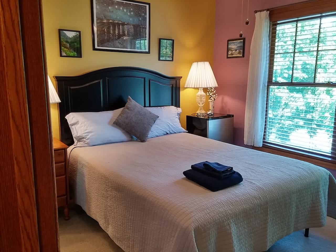 Your bedroom is on the second floor (mini-fridge to the right of the bed), with a large window that looks out on our front yard and the quiet street beyond.