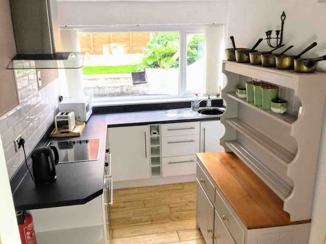 Fully fitted kitchen and decorative brass pan ware.