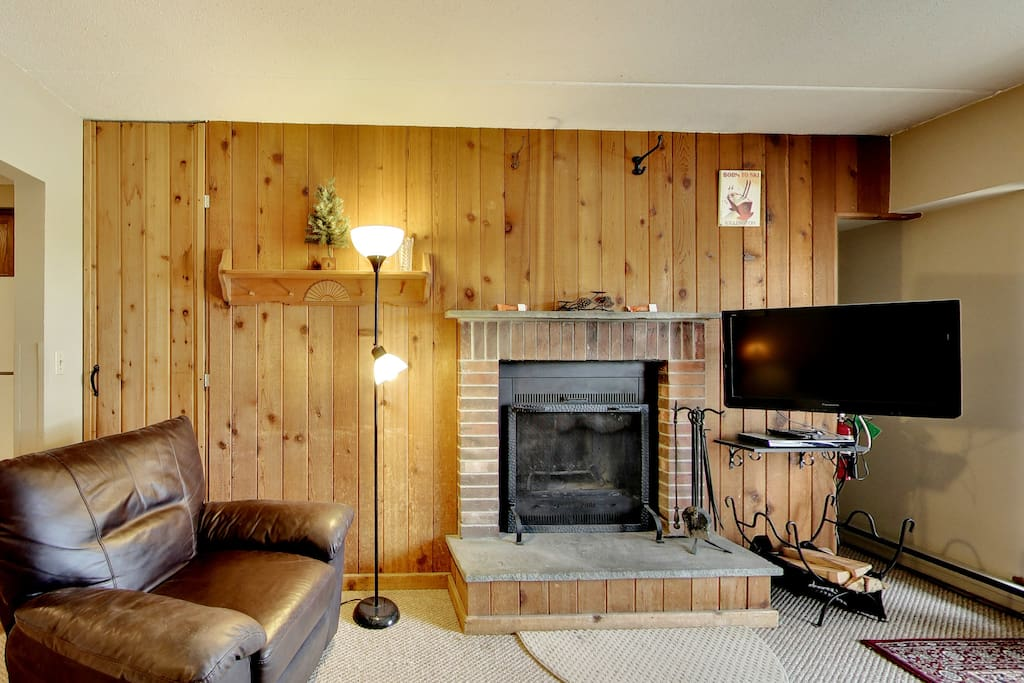 Living Room With TV and Large Wood Burning Fireplace