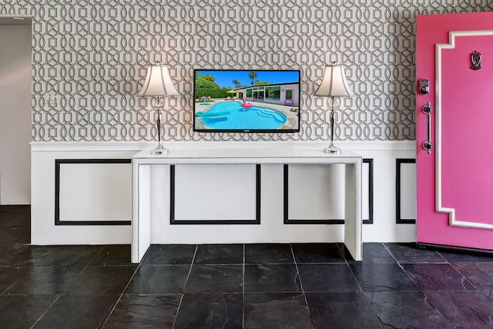 "Front entry with wainscoting, Brewster wallpaper, white ostrich print entry table, 37"" flatscreen smart tv and nickel plated hardware"