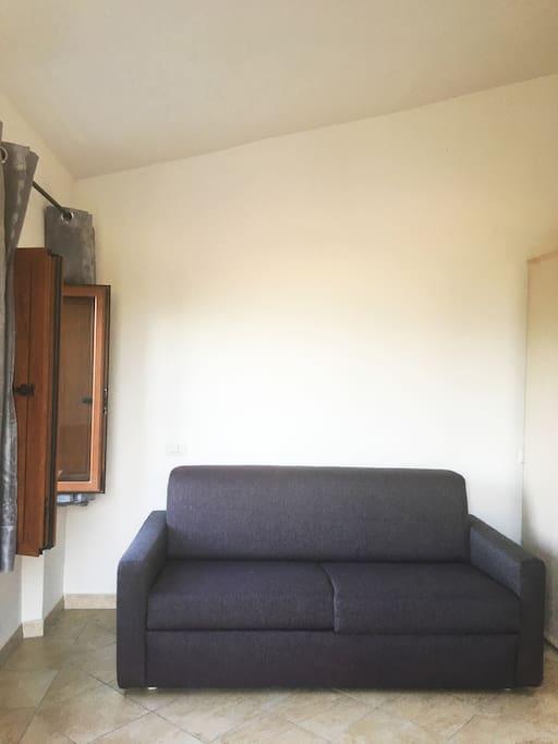 Dettaglio entrata con divano letto. / Entrance detail with sofa bed.