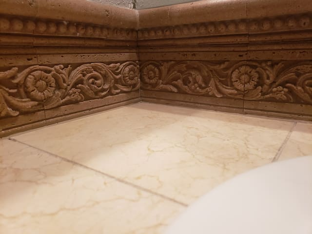 Intricate trim on the bathroom counter and inside the shower.