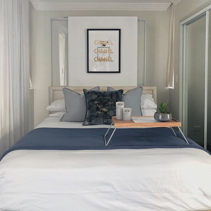 Comfortable queen size bed with Coco Chanel accents. A large mirror wardrobe, and additional storage behind the bed.