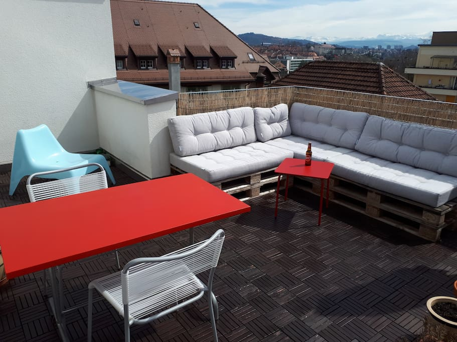 Big terrace with lounge, table and view of the alps