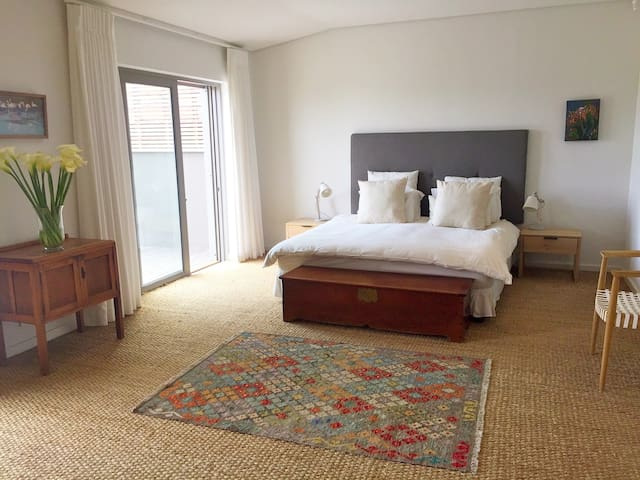 Master bedroom 1 (king) with en suite bathroom (downstairs). Two sliding doors open out onto a deck area with sea views.