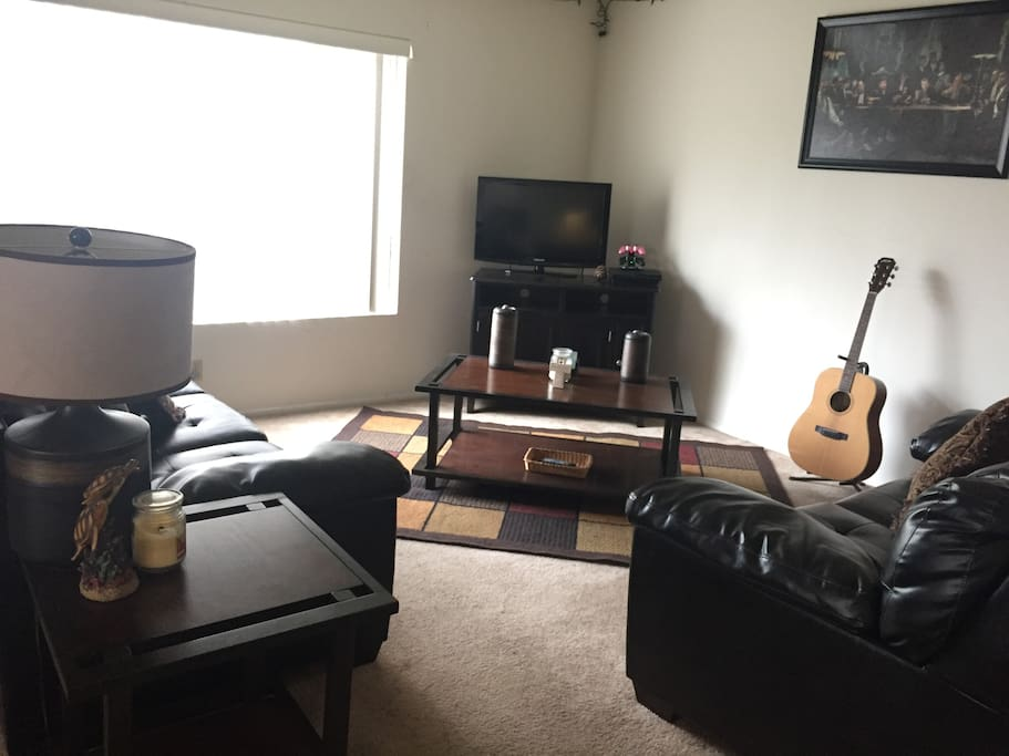 Living Room, with 2 leather couches, television, and large coffee table.