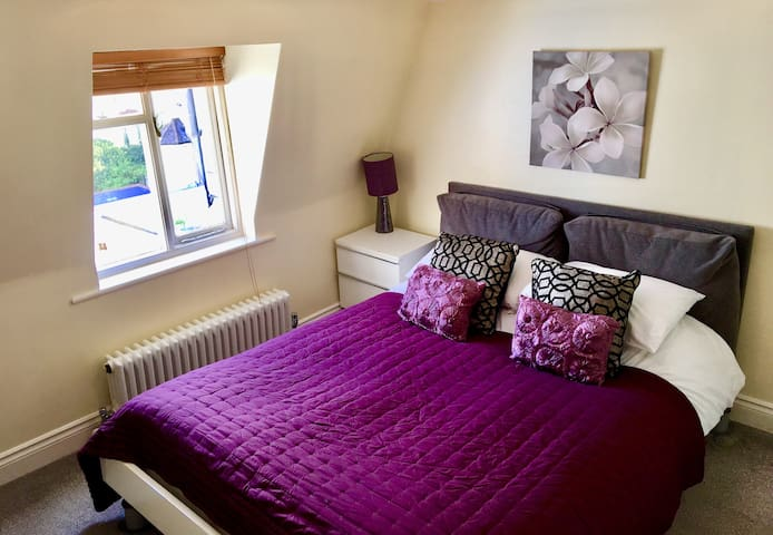 The cosy master bedroom has a comfortable kingsize bed, hanging rail, sloping floors throughout and views over Kemp Town's rooftops.
