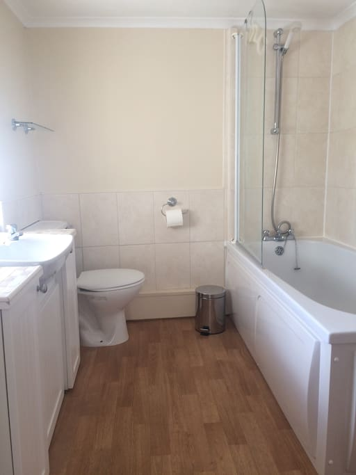 Shared bathroom with bath and shower.