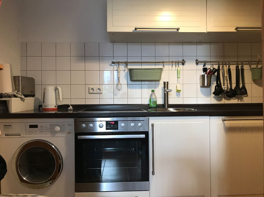 Well equipped kitchen with modern induction oven, dish washer and washer dryer combo
