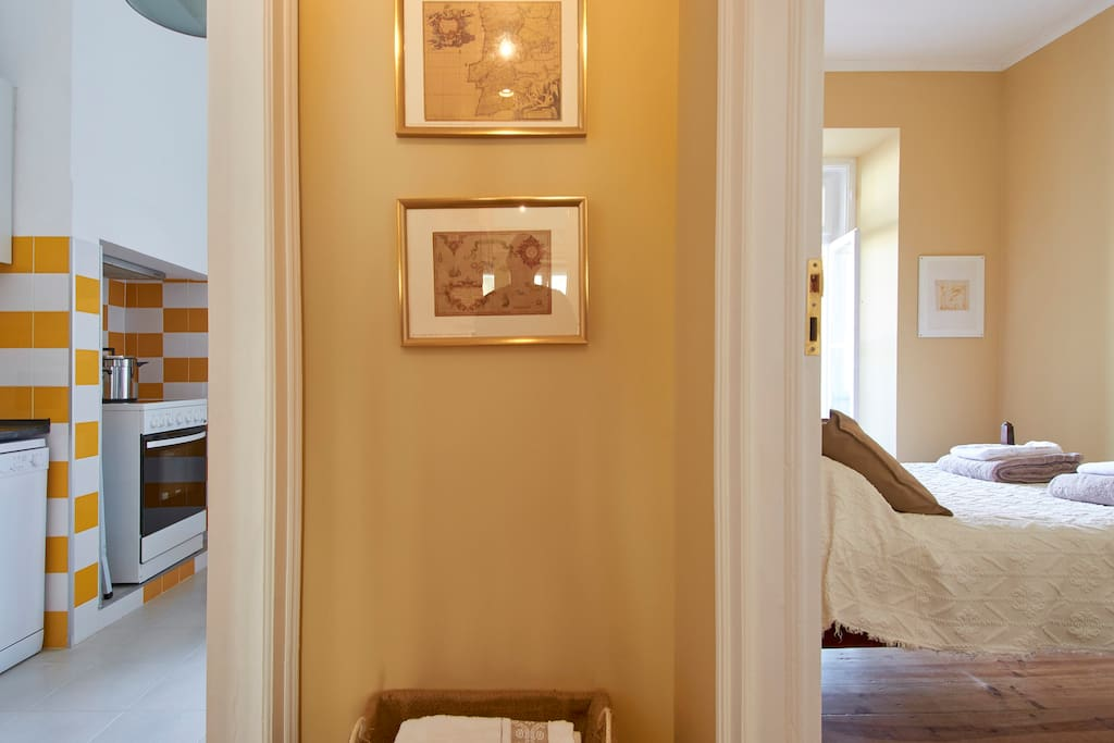 A narrow corridor leads from the main entrance to both kitchen and main bedroom