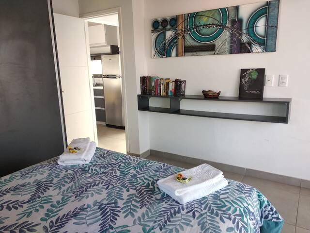 Dormitorio Matrimonial con Cama Queen y placar amplio, ventana con vista de los pinos que rodean la propiedad y un balcon privado
