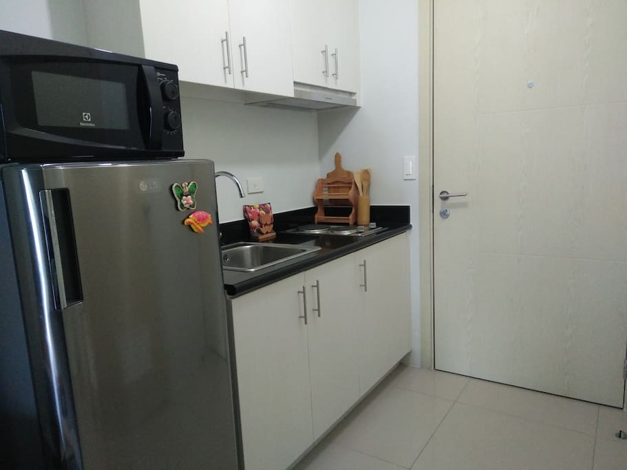 The kitchen with a small electrical stove, a fridge and a microwave oven