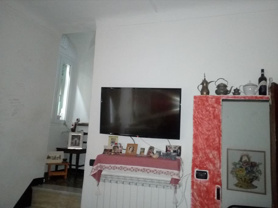 Tv a parete. Sulla sinistra la scala di accesso ai piani superiori