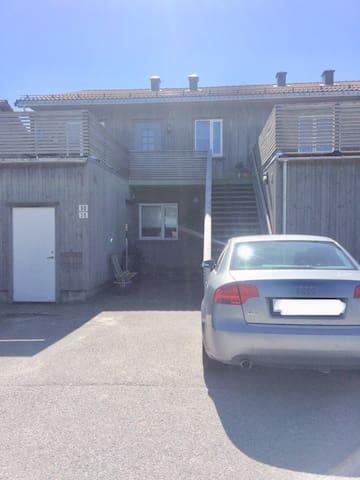 Inngangsparti. En parkeringsplass tilhørende leiligheten foran trappen.