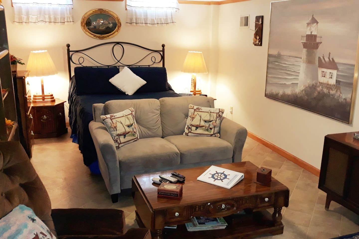 Living room/bedroom area includes a queen bed; chest; end tables; chair; large screen tv with cable; love seat; roll-away bed; and electric fireplace.