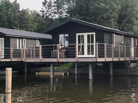 Havenhuis + bootje in Friesland aan de Fluessen