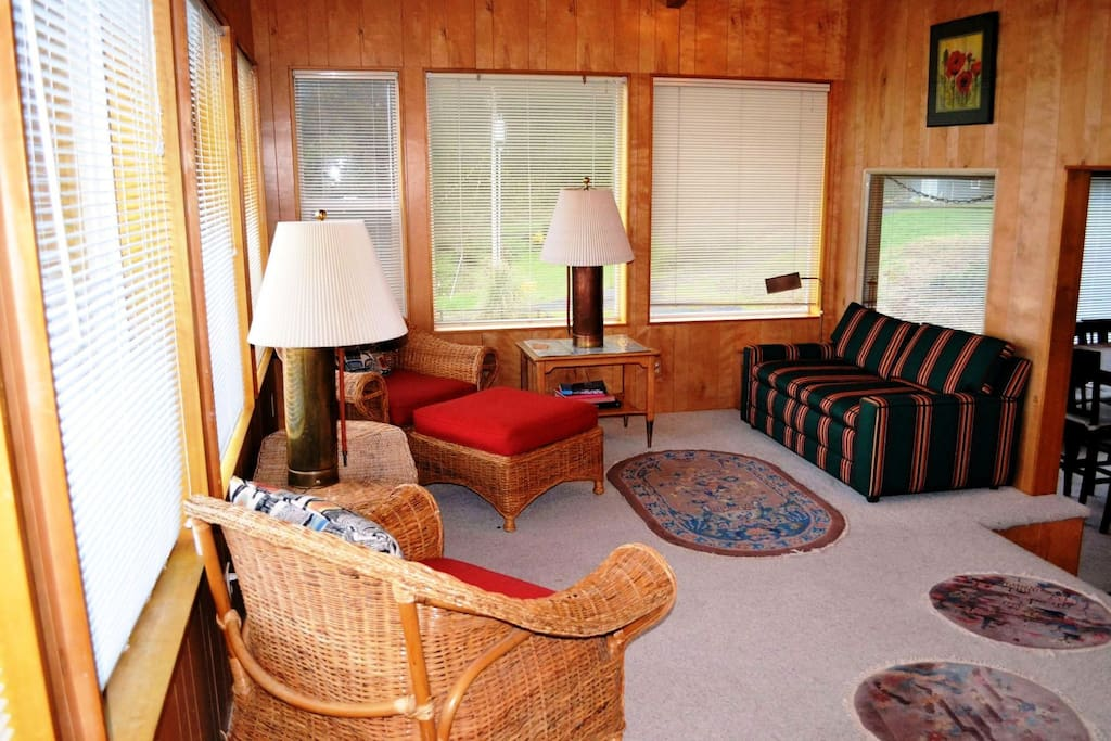 Entry sun room with spectacular ocean views, hide-a-bed couch and two wicker chairs.