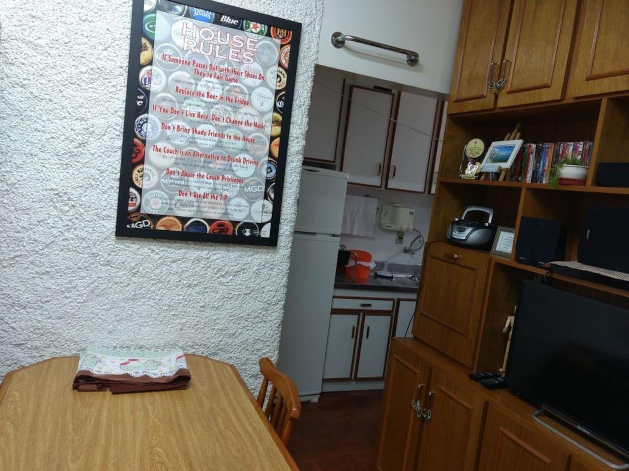Sala de estar com mesa para refeições, TV, mesa de escritório e wi-fi.