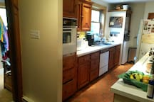 Kitchen with dishwasher, microwave, standard oven, 4 cooking elements, washer, dryer. Mud room/main entrance on left.
