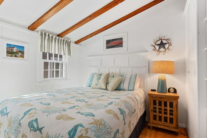 Queen size bed in 1st floor bedroom. Nightstand equipped with convenient power strip with USB ports and standard outlets for charging your devices.
