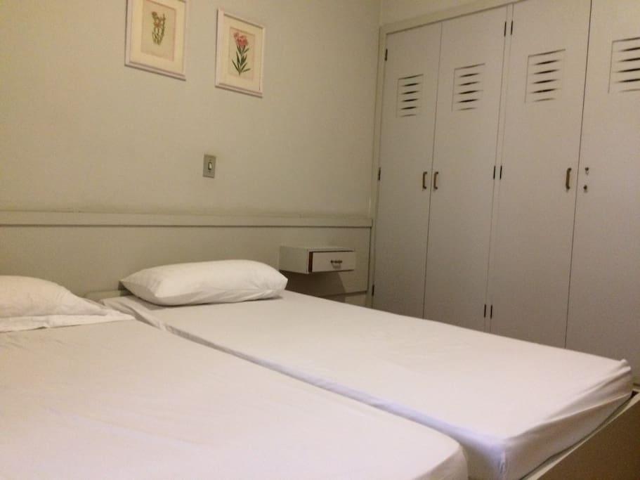 Quarto com duas camas de solteiro e um colchão. Com ar-condicionado