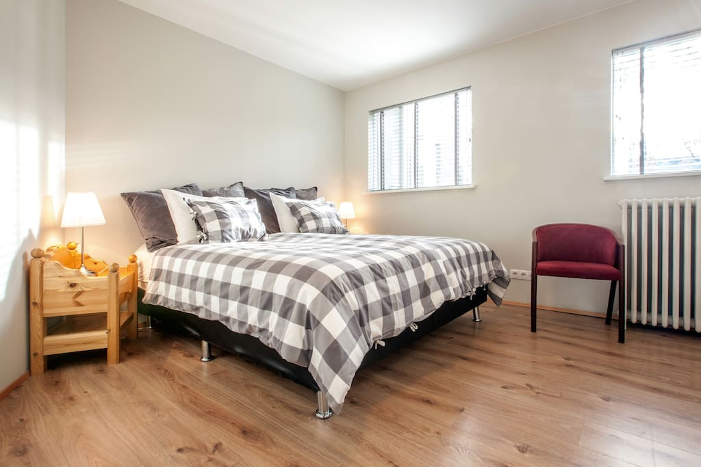 A queen size bed (180x203 cm / 60  xi 80 inches).  Two nightstands, classic Scandinavian pine. Windows facing garden (direction southeast),  can be left slightly open yet locked.