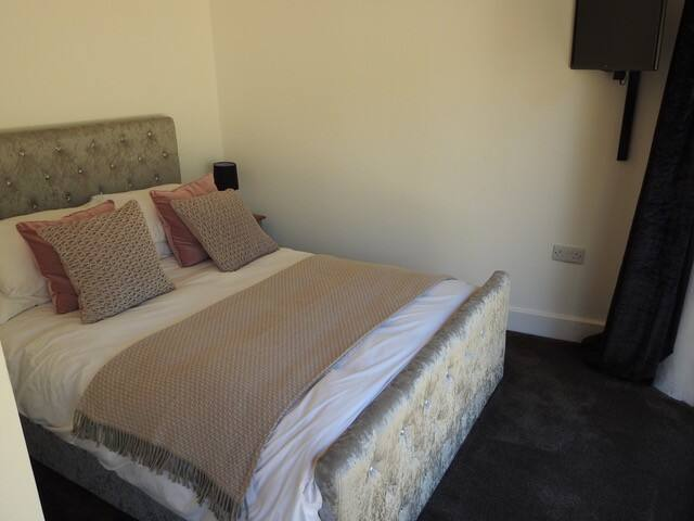 a touch of luxury in the bedroom with double bed and wall mounted TV. Draw back the curtains to reveal double doors with views into the private garden.