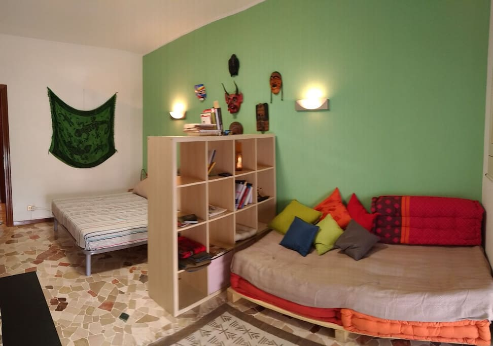 Room includes living area with sofa that can turn into single bed