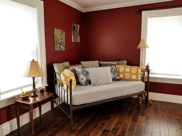 Living room has a single size daybed with comfy cushions,  a medium firm memory foam mattress.