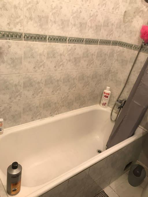 Salle de bain fonctionnelle, avec baignoire et machine à laver. Les serviettes de bains sont fournies également.