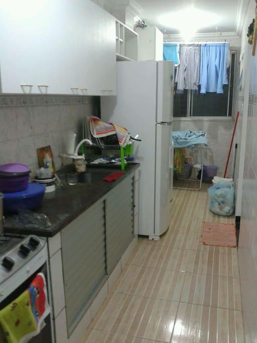 cozinha com fogão, geladeira, armarios, tanque e máquina de lavar.